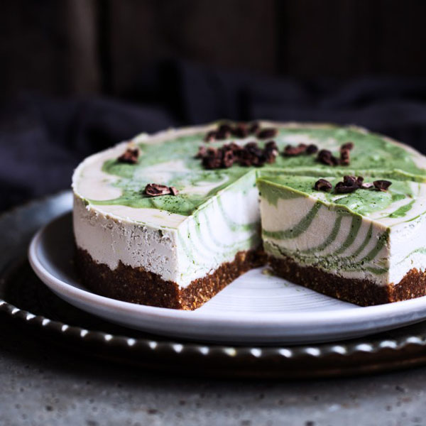 Vegan matcha zebra cheesecake with a slice missing