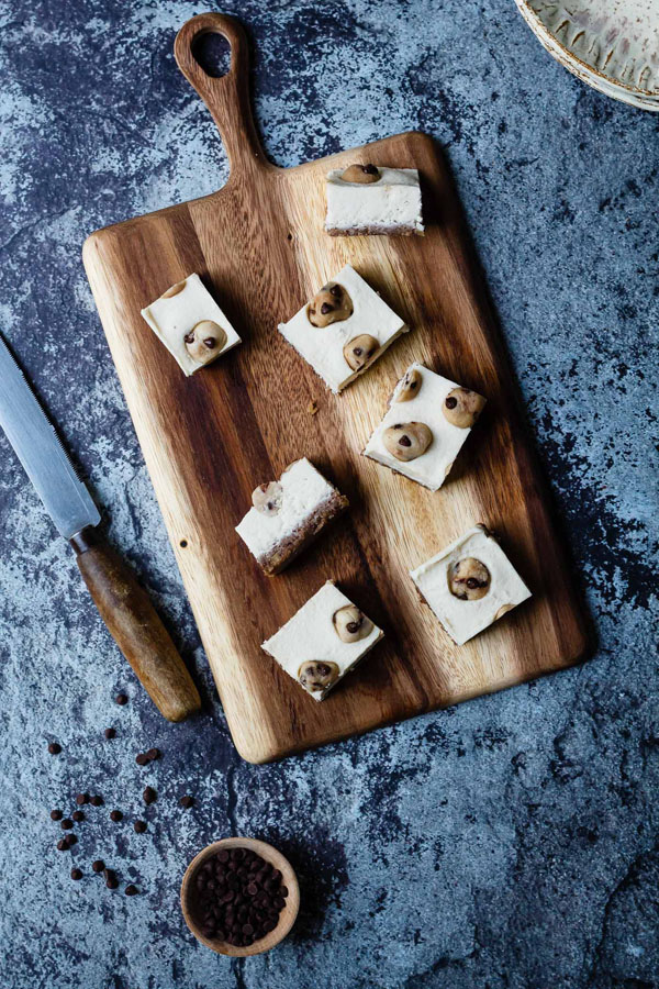 Cookie dough cheesecake bars presented on a board