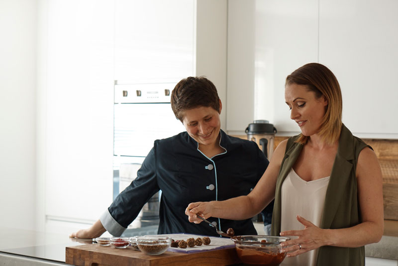 Amy Levin advising a student in the art of making chocolate